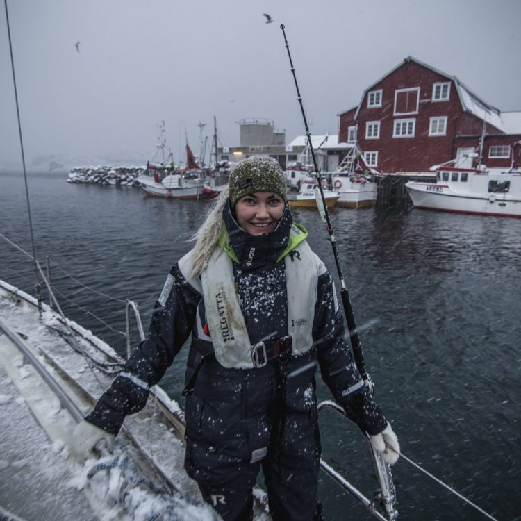 girl with snow in her hair sailing in arctic lofoten during winter