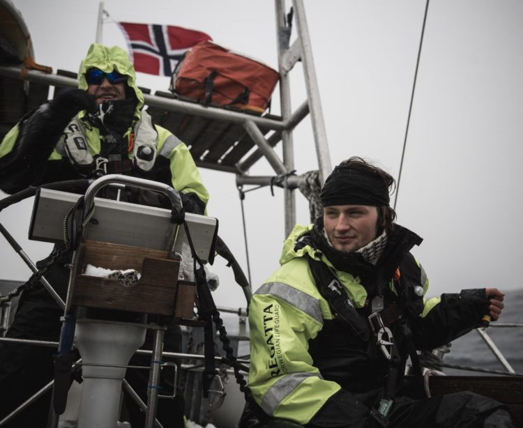 boys sailing in rough conditions in lofoten norway arctic winter