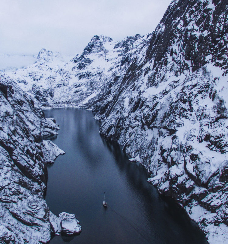 drone shot of the sailboat and trollfjord in lofoten norway misty weather